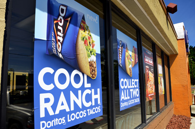 Usually, I can walk past the Taco Bell at Augusta and Mills Avenue without giving what it represents much thought, but today I couldn't help myself. I actually read those big banners they've had hanging in the windows there for weeks, the ones encouraging me to eat junk food-flavored fast food.