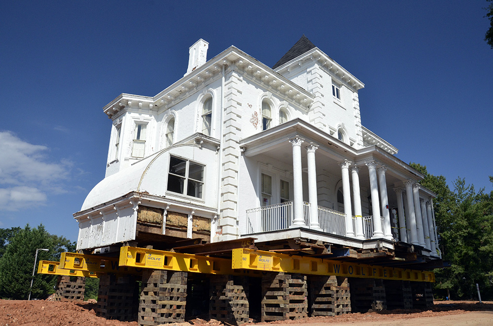 The Wilkins House, raised and resting on beams at its soon to be former location facing Augusta Street.